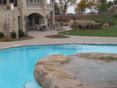 Usually placed on a concrete base, we design and install custom created stone pool patios and stone pool decks.